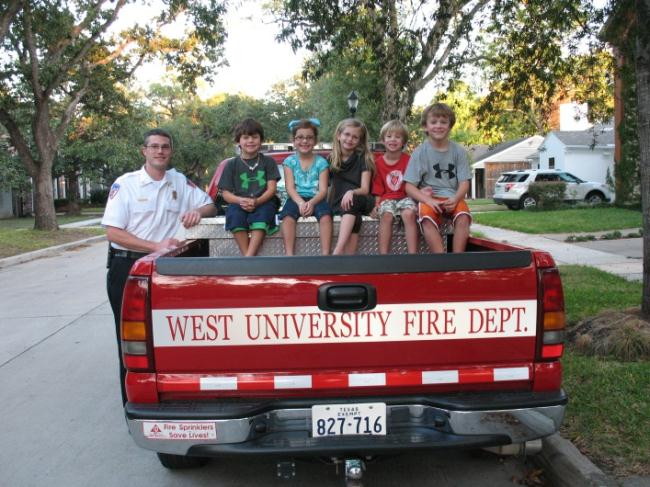 5 children sitting in the bed of a Fire Department truck
