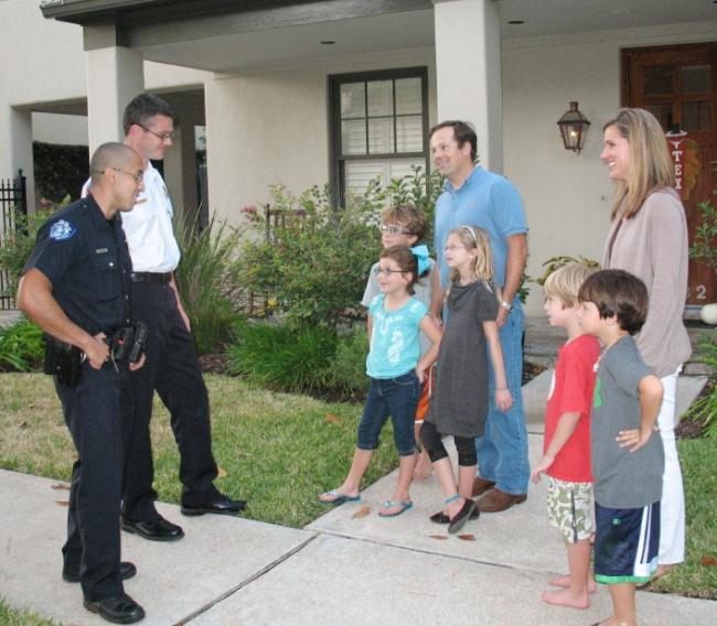 Police officers talking with children and adults