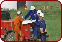 4 constructions workers going over plans on the back of a truck in the field