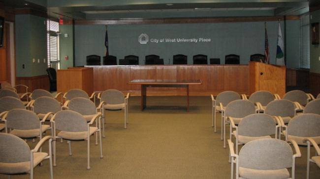 View of the City Council Chambers with a podium and chairs in rows