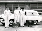 Black and white photo of 3 men in hats and uniforms standing next to a car