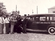 Sepia toned photo of men standing next to a long car