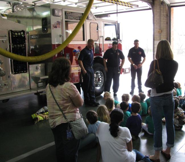 Firefighters showing children a fire engine