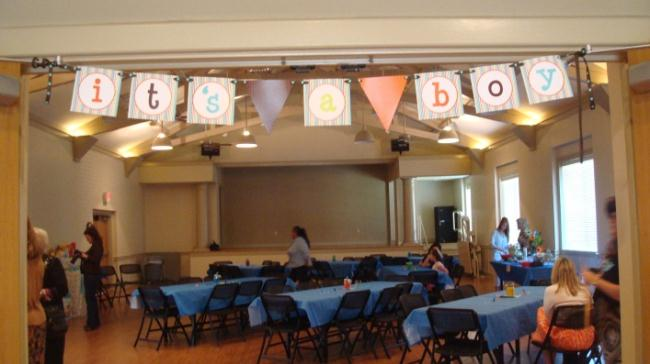 It&#39s a Boy banner stretches over a room decorated for a baby shower