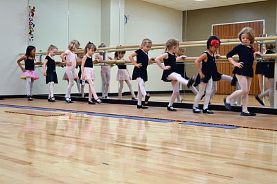 A line of children in leotards dance at a ballet barre